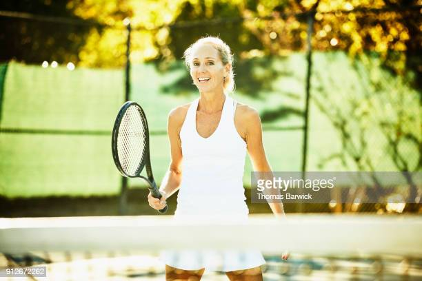 Smiling mature female tennis player standing at net during early morning match