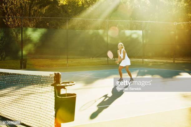 Smiling mature female tennis player waiting for return at net during tennis match