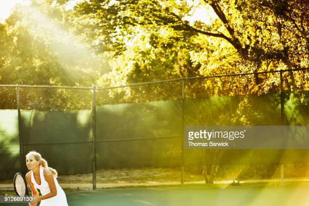 Smiling mature female tennis player waiting to return serve during early morning tennis match