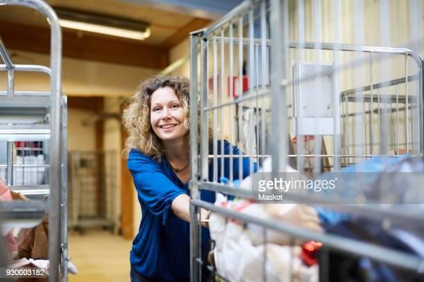 smiling mature female volunteer pushing cart while looking away at warehouse - liefdadigheidswerk stockfoto's en -beelden