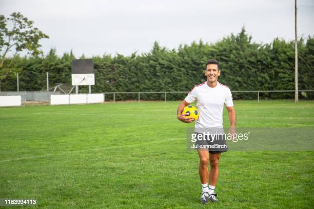 smiling mature footballer walking across field with ball - sports jersey stock pictures, royalty-free photos & images