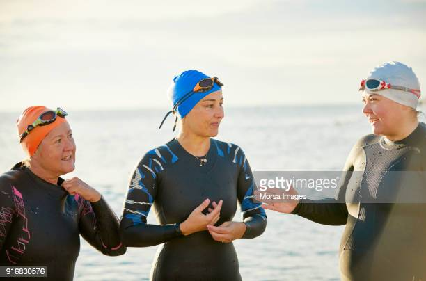 smiling mature friends talking at beach - sea swimming stock photos and pictures