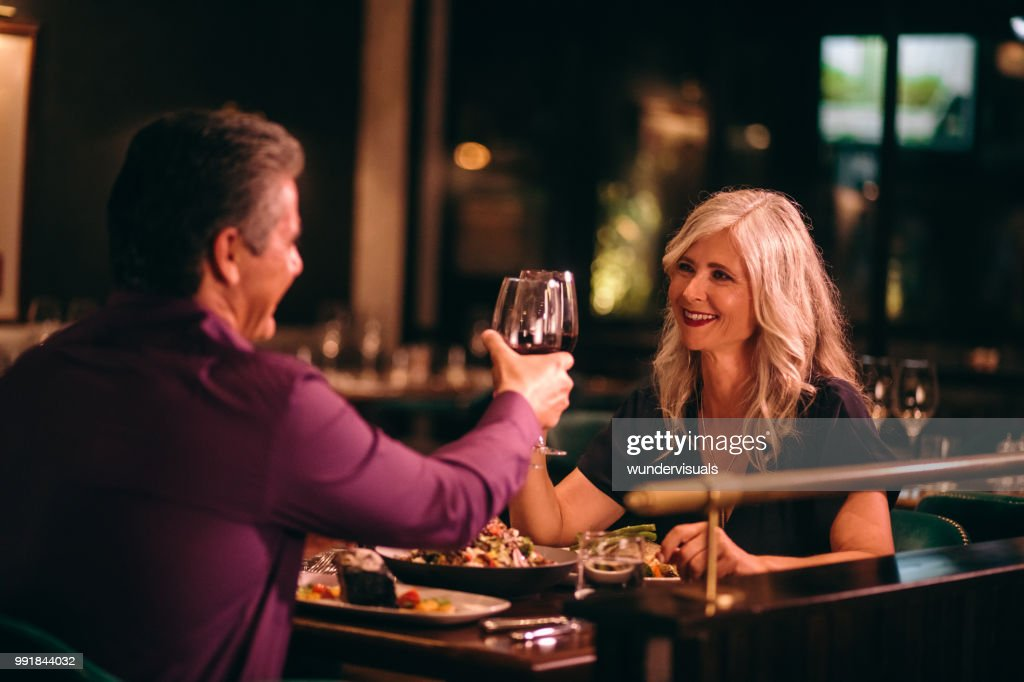 Smiling mature husband and wife toasting with wine at dinner : Stock Photo