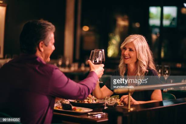 smiling mature husband and wife toasting with wine at dinner - anniversary stock pictures, royalty-free photos & images