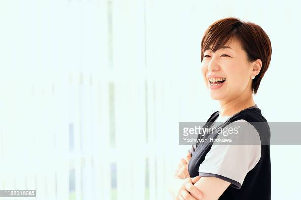 smiling mature japanese woman in fitness studio - 女性 ストックフォトと画像