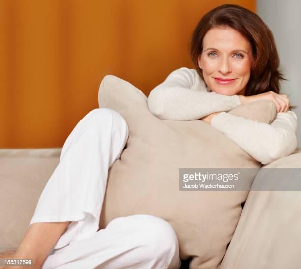 smiling mature lady cuddling a pillow on couch - bruin haar stockfoto's en -beelden