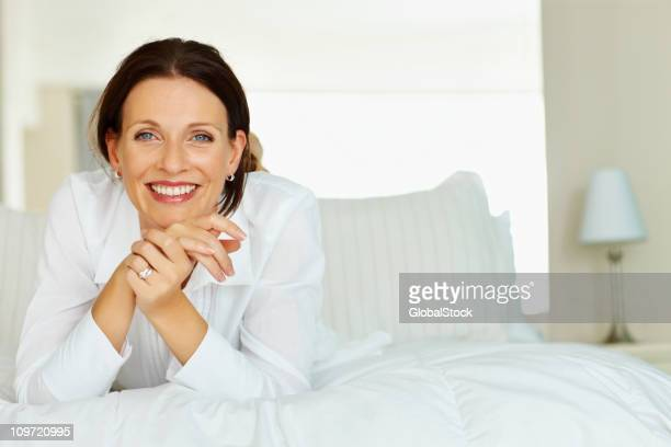 Smiling mature lady leans chin on her hands whilst on bed