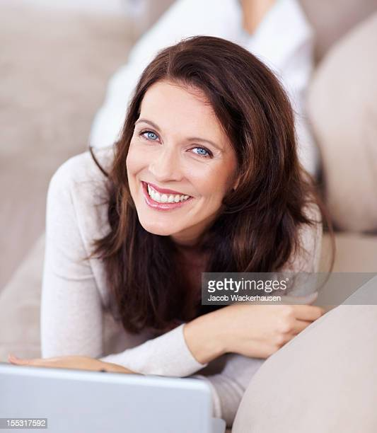 smiling mature lady lying on couch and using laptop - brown hair stock pictures, royalty-free photos & images