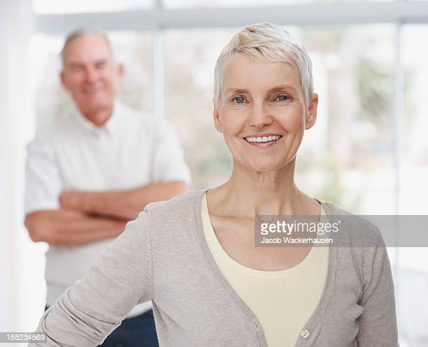 Smiling mature lady with husband in the background