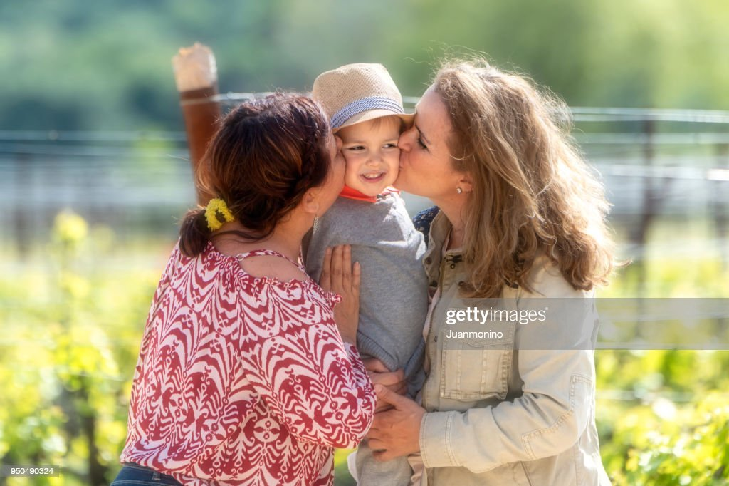 Smiling Mature Lesbian Couple Posing With Their Son Stock Photo