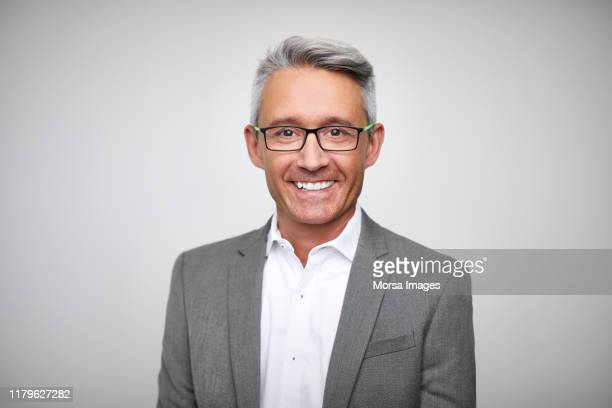smiling mature male ceo wearing gray suit - businessman stock pictures, royalty-free photos & images