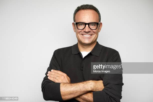smiling mature male ceo with arms crossed - portrait classique photos et images de collection