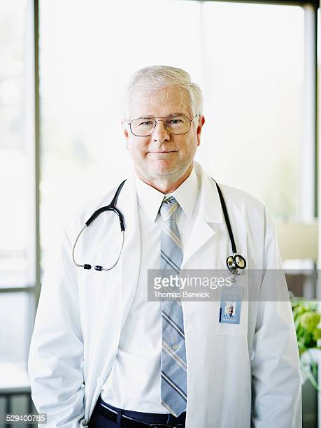 Smiling mature male doctor standing in hospital