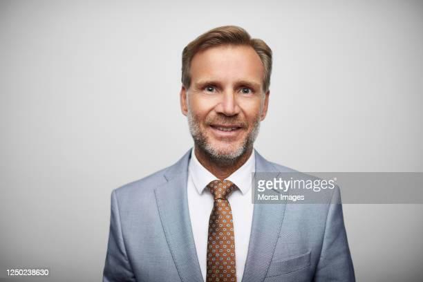 smiling mature male leader wearing blue suit. - anzug stock-fotos und bilder