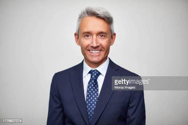 smiling mature male leader wearing navy blue suit - anzug stock-fotos und bilder