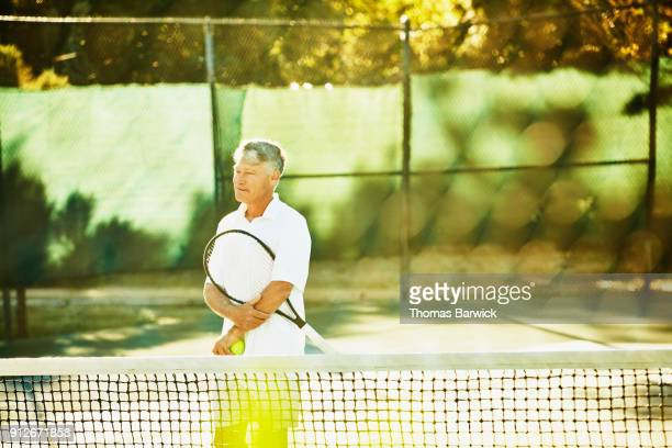 Smiling mature male tennis player in discussion with playing partner at net after match