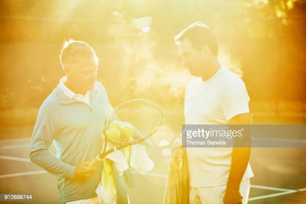 Smiling mature male tennis player listening to coach after early morning workout