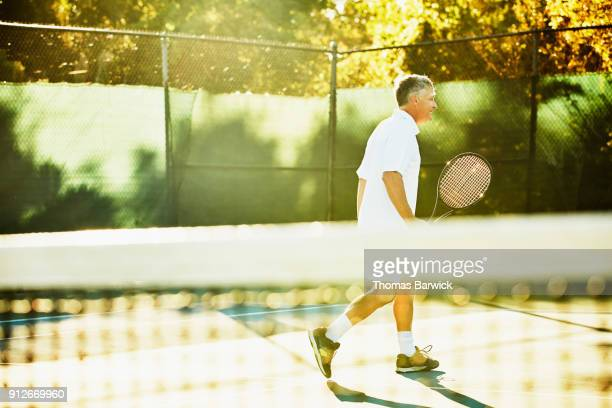 Smiling mature male tennis player walking away from net in between points during early morning tennis match