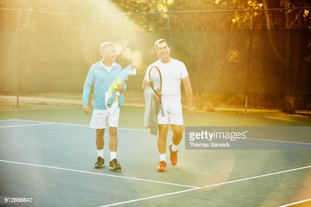 Smiling mature male tennis players walking off court after early morning tennis match
