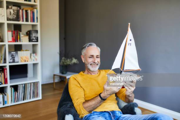 smiling mature man at home holding model sailboat - ship in a bottle stock pictures, royalty-free photos & images