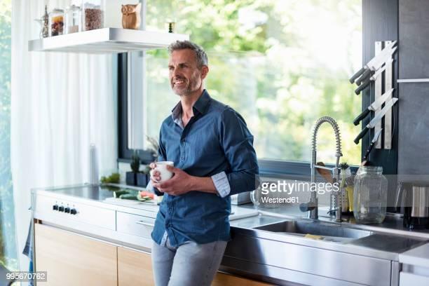 smiling mature man at home in kitchen with cup of coffee - mann kaffee stock-fotos und bilder