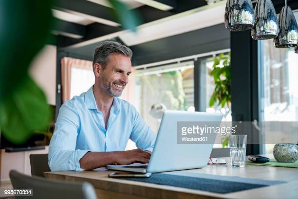 smiling mature man at home using a laptop at table - usare il laptop foto e immagini stock