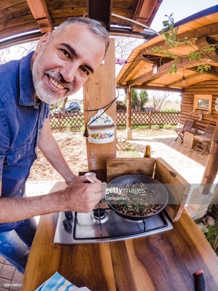 Lächelnde reifer Mann in Outdoor-Küche Kochen : Stock-Foto