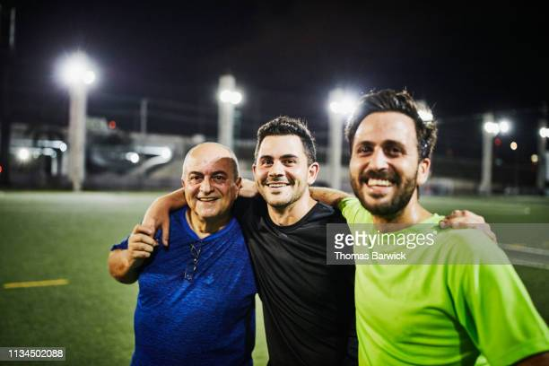 smiling mature man embracing adult sons after evening soccer match - nosotroscollection stock pictures, royalty-free photos & images