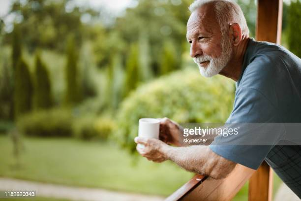smiling mature man enjoying in morning coffee on a terrace. - contemplation outside stock pictures, royalty-free photos & images
