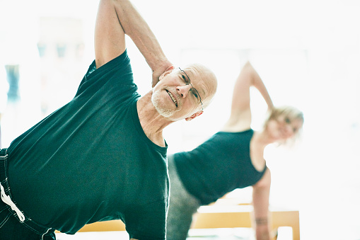 Smiling mature man exercising during pilates class in fitness studio - gettyimageskorea