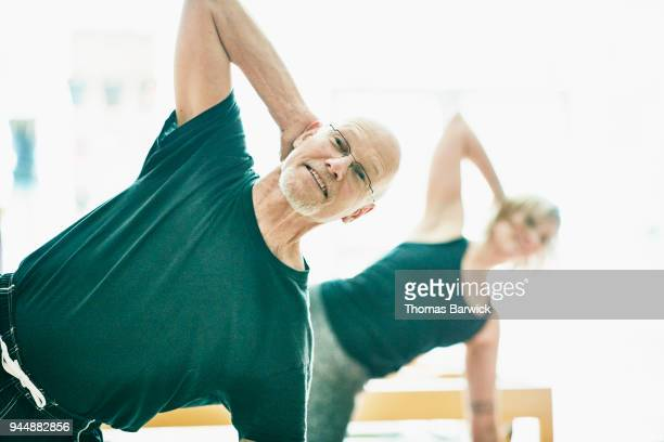 Smiling mature man exercising during pilates class in fitness studio