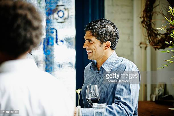 Smiling mature man in discussion at restaurant bar