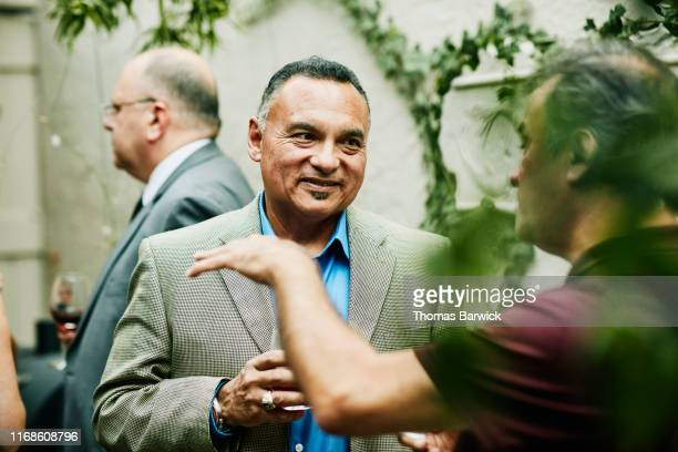 smiling mature man in discussion with friend during cocktail party - latin american and hispanic stock pictures, royalty-free photos & images