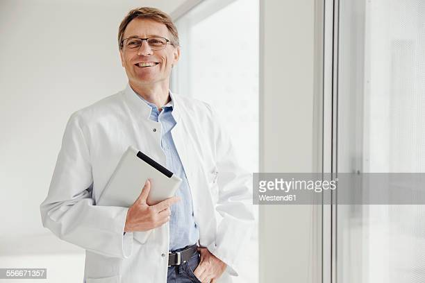 Smiling mature man in lab coat holding digital tablet at the window