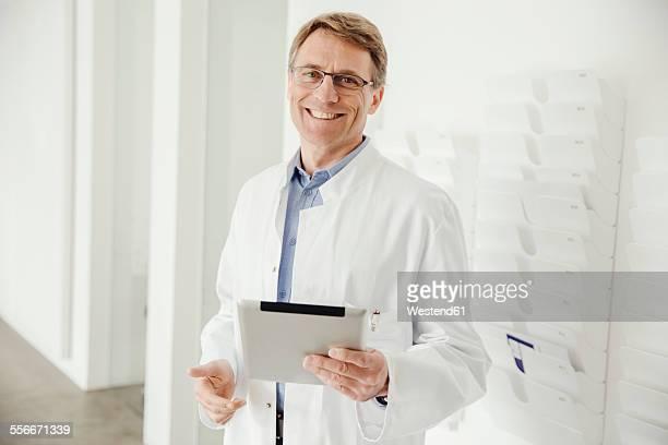 Smiling mature man in lab coat holding digital tablet