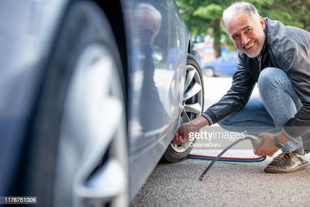 smiling mature man inflating car tires outdoors - inflating stock pictures, royalty-free photos & images