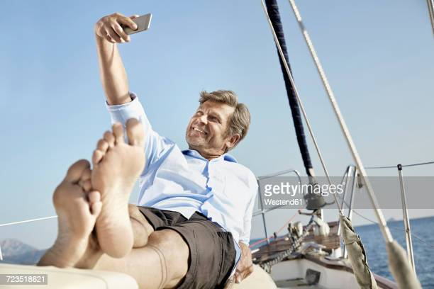 smiling mature man lying on deck of his sailing boat taking selfie with cell phone - soles pose stockfoto's en -beelden