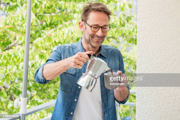 Smiling mature man on balcony pouring coffee in a cup