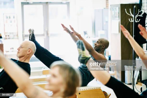 Smiling mature man practicing teasers on pilates chair during class in fitness studio