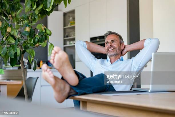 smiling mature man relaxing at home with laptop on table - stubble stock pictures, royalty-free photos & images