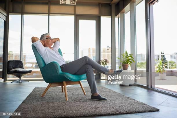 smiling mature man relaxing in armchair at the window at home - pessoas serenas - fotografias e filmes do acervo