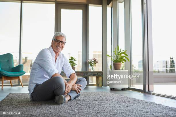 smiling mature man relaxing sitting on carpet at home - 胡坐 ストックフォトと画像