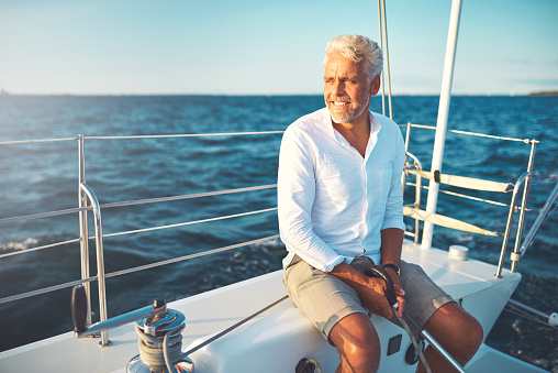 Smiling mature man sailing his yacht on a sunny day 947296986