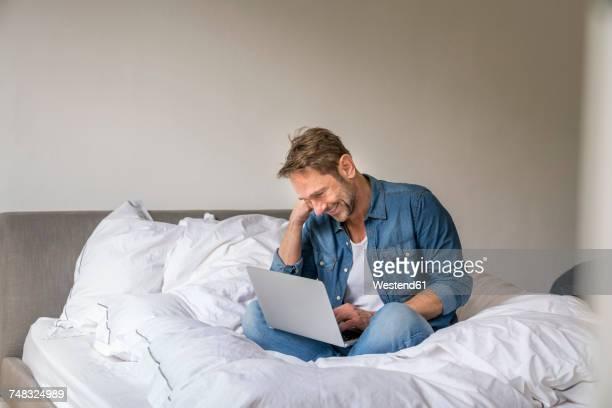 Smiling mature man sitting on his bed using laptop