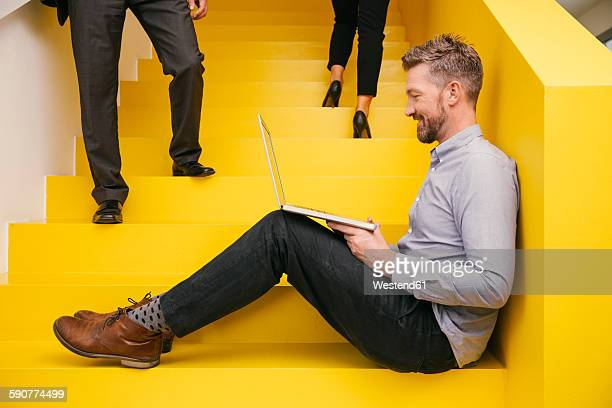 smiling mature man sitting on yellow stairs with his laptop - gelb stock-fotos und bilder