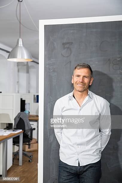 Smiling mature man standing at blackboard in office