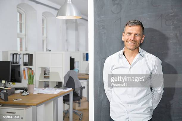 smiling mature man standing at blackboard in office - hands behind back stock pictures, royalty-free photos & images