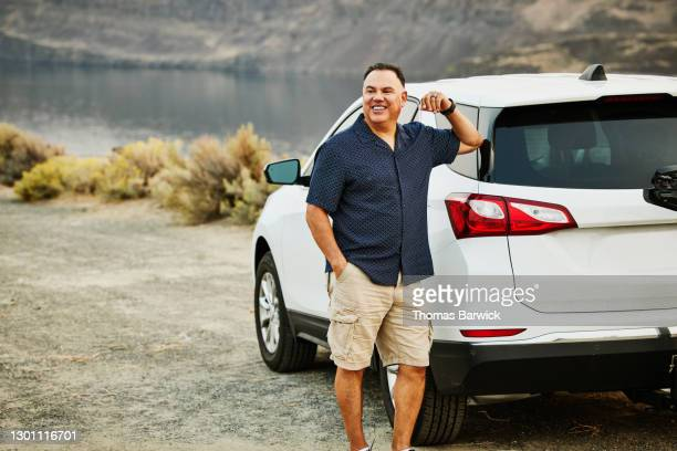 smiling mature man standing next to car during road trip - next to stock pictures, royalty-free photos & images