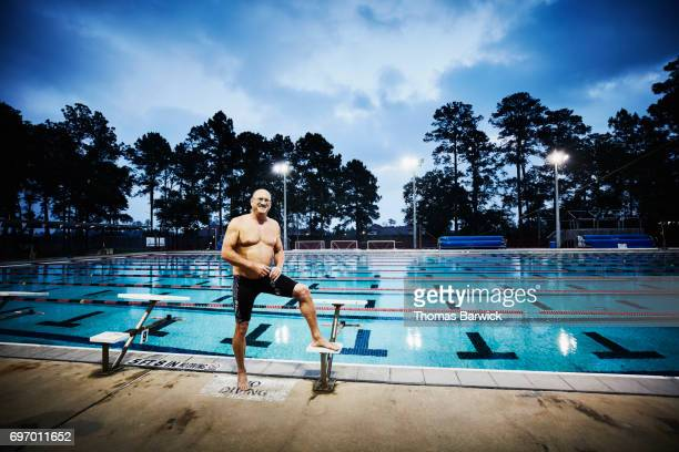 Smiling mature man standing on deck of outdoor pool before early morning workout