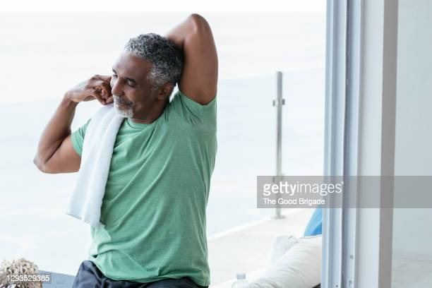 smiling mature man stretching in balcony - men exercising stock pictures, royalty-free photos & images